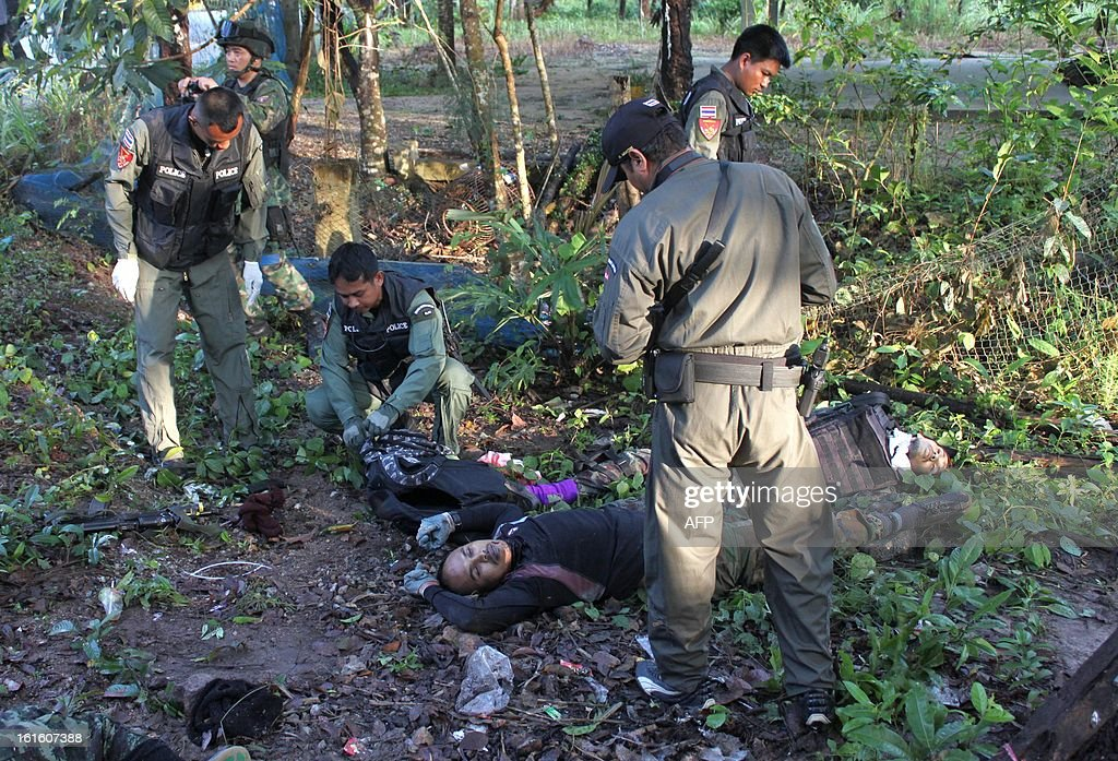 Thai police officers inspect dead suspected insurgents who were killed when they attacked a military base in Thailand's restive southern province of Narathiwat on February, 13, 2013. Scores of heavily armed gunmen stormed a military base in unrest-plagued southern Thailand, an army spokesman said, in a major assault that left at least 16 militants dead. AFP PHOTO /MADAREE TOHLALA