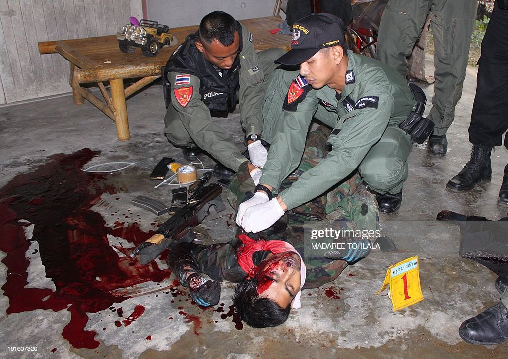 Thai police officers inspect one of the dead body of suspected insurgents who were killed when they attacked a military base in Thailand's restive southern province of Narathiwat on February, 13, 2013. Scores of heavily armed gunmen stormed a military base in unrest-plagued southern Thailand, an army spokesman said, in a major assault that left at least 16 militants dead.