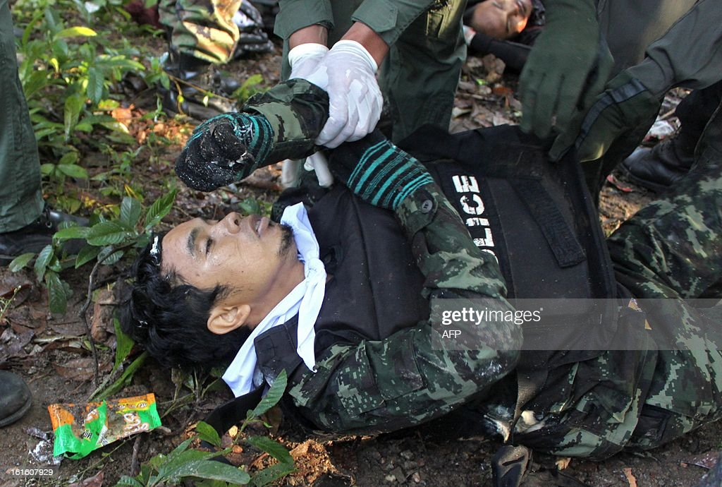 Thai police officers inspect one of the dead suspected insurgents who were killed when they attacked a military base in Thailand's restive southern province of Narathiwat on February, 13, 2013. Scores of heavily armed gunmen stormed a military base in unrest-plagued southern Thailand, an army spokesman said, in a major assault that left at least 16 militants dead. AFP PHOTO /MADAREE TOHLALA