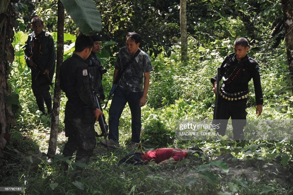 Thai police officers inspect the area around the body of a suspected separatist militant (C) who was shot dead during a clash with army rangers in the Cha-nea district of Thailand's restive southern province of Narathiwat on April 30, 2013. More than 5,500 people have been killed in Thailand's Muslim-majority south since 2004, with shadowy insurgent groups blamed for near-daily bombings and shootings. AFP PHOTO / Madaree TOHLALA