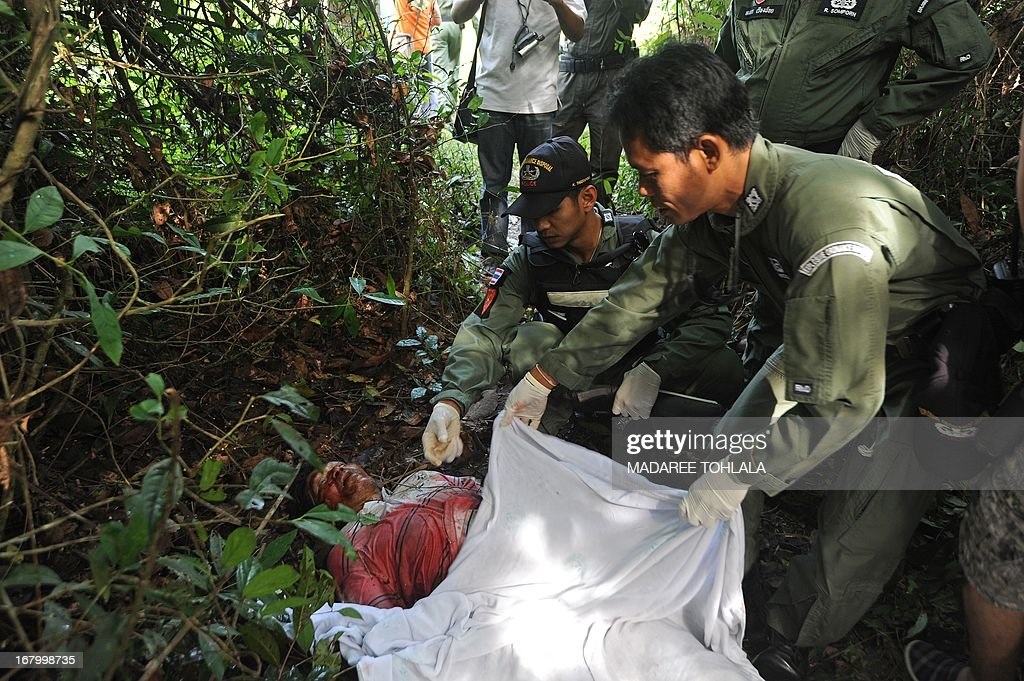 Thai police officers inspect the body of a Muslim truck driver who was shot dead by suspected separatist militants in the Rueso district of Thailand's restive southern province of Narathiwat on May 4, 2013. More than 5,500 people have been killed in near-daily bombings and shootings in three Muslim-majority provinces near Thailand's southern border with Malaysia since 2004. AFP PHOTO/Madaree TOHLALA
