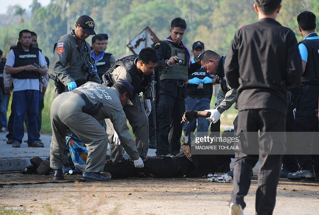 Thai police officers inspect the body of a Ranger who was killed in a roadside bomb attack by suspected separatist militants in Thailand's restive southern province of Narathiwat on March 28, 2013. Thailand opened its first formal peace talks with a rebel group from its insurgency-wracked south on March 28, as a fresh bombing killed three people in a stark reminder of the difficulties negotiators face. AFP PHOTO/Madaree TOHLALA