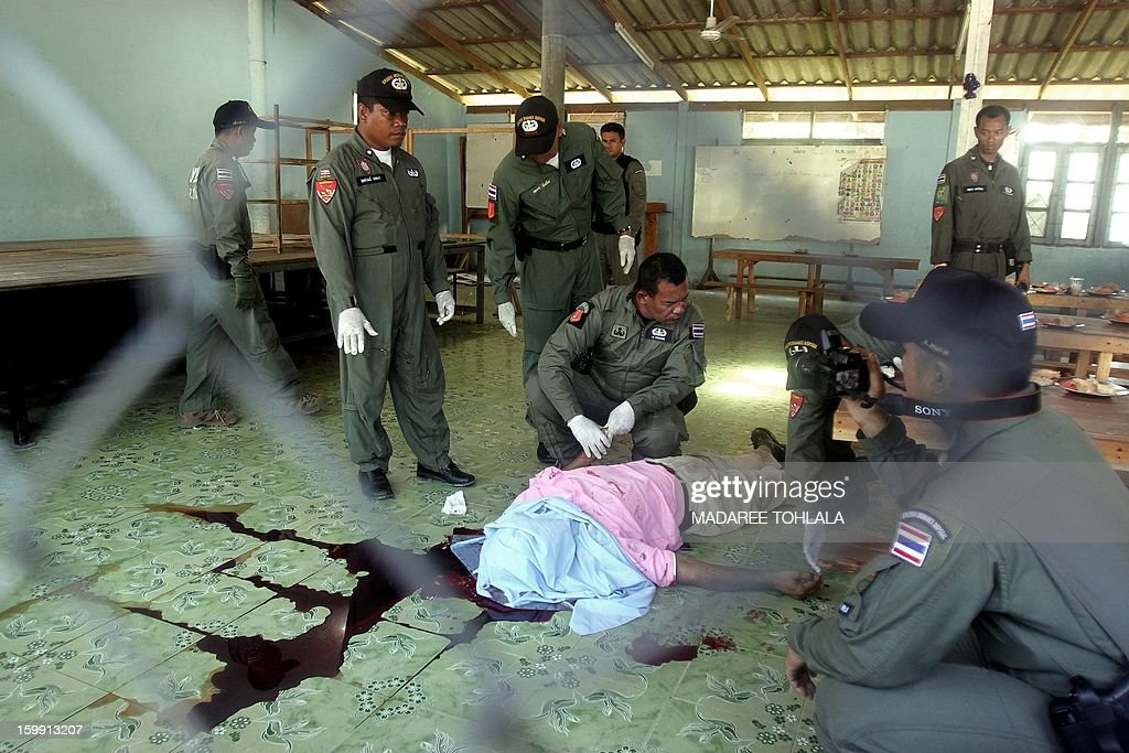 Thai police officers inspect the body of a slain Thai Muslim teacher who was shot dead in front of dozens of children by suspected separatist militants at the school cafeteria in Thailand's restive southern province of Narathiwat on January 23, 2013. Near daily attacks -- including shootings, bombings and even beheadings -- mean violence is a part of life for many in Thailand's far south. More than 5,300 people, both Buddhist and Muslim, have been killed since 2004, according to local conflict monitor Deep South Watch. AFP PHOTO/Madaree TOHLALA
