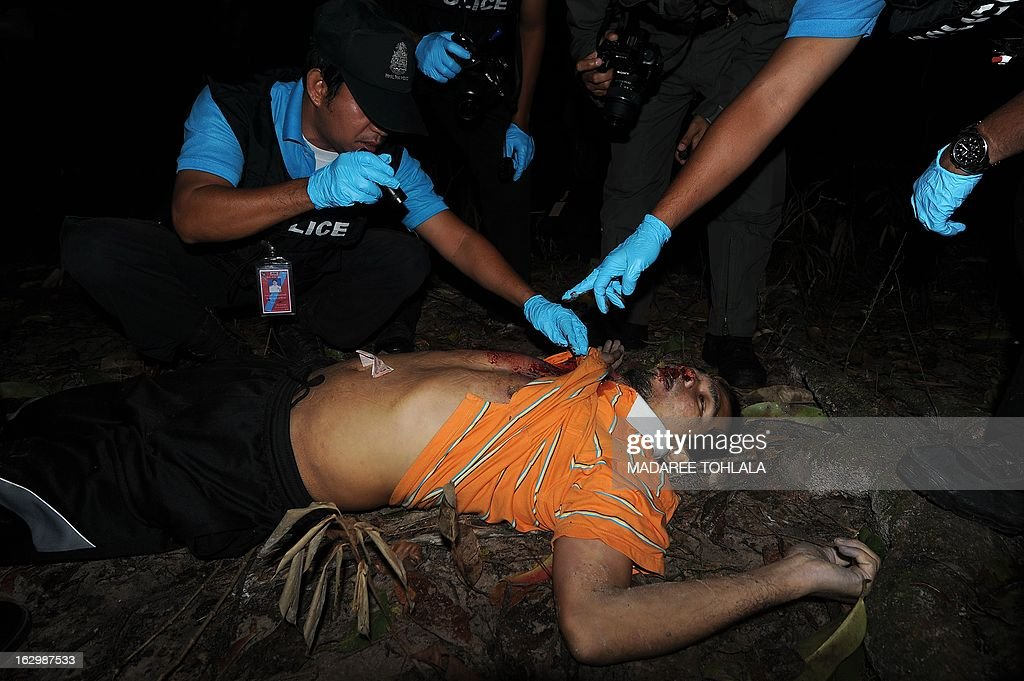 Thai police officers inspect the body (C) of a suspected Muslim militant shot dead during a clash with soldiers in Thailand's restive southern province of Narathiwat on March 3, 2013. A stubborn insurgency seeking greater autonomy has raged across several provinces in the south of Thailand bordering Malaysia for nine years, with near-daily shootings and bombings. AFP PHOTO / Madaree TOHLALA