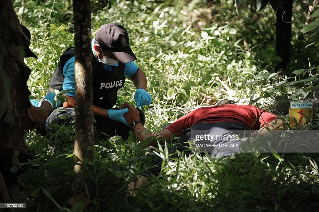 Thai police officers inspect the body of a suspected separatist militant (R) who was shot dead during a clash with army rangers in the Cha-nea district of Thailand's restive southern province of Narathiwat on April 30, 2013. More than 5,500 people have been killed in Thailand's Muslim-majority south since 2004, with shadowy insurgent groups blamed for near-daily bombings and shootings. AFP PHOTO / Madaree TOHLALA