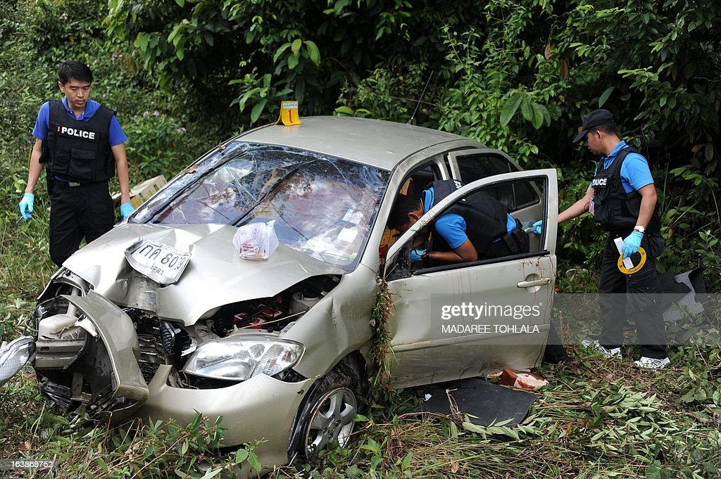 Thai police officers inspect the car of a Muslim official who was shot dead by suspected separatist militants in Thailand's restive southern province of Narathiwat on March 17, 2013. A stubborn insurgency seeking greater autonomy has raged across several provinces in the south of Thailand bordering Malaysia for nine years -- with near-daily shootings and bombings. AFP PHOTO/Madaree TOHLALA
