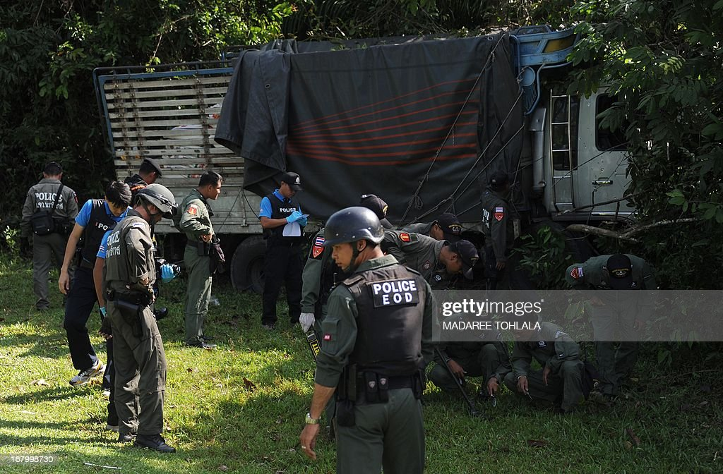 Thai police officers inspect the site of an attack in which a Muslim truck driver was shot dead by suspected separatist militants in the Rueso district of Thailand's restive southern province of Narathiwat on May 4, 2013. More than 5,500 people have been killed in near-daily bombings and shootings in three Muslim-majority provinces near Thailand's southern border with Malaysia since 2004. AFP PHOTO/Madaree TOHLALA