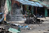 Thai police officers inspect the wreckage of a car bomb detonated by suspected separatist militants in Thailand's restive southern province of...