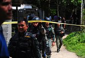 Thai police officers leave the home of an suspected insurgent after a deadly clash between Islamic insurgents and soldiers in the Rueso district of...