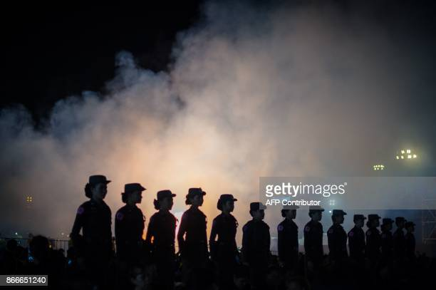 Thai police stand at attention as smoke from artillery gun salvos rises in the air near the cremation grounds where the body of late Thai King...