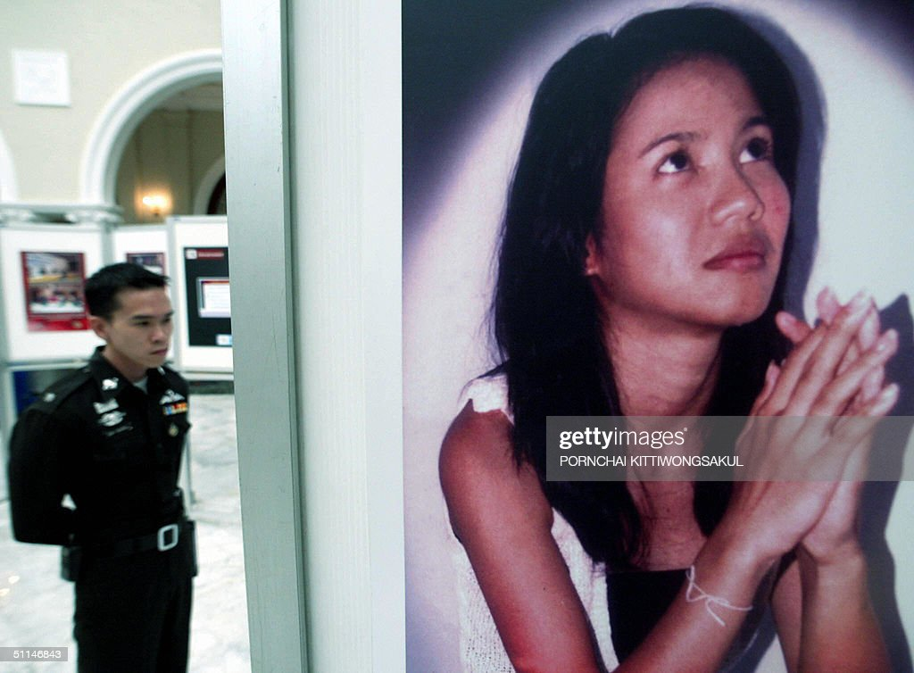 Thai policeman looks at an exhibition of photos during the opening of the national workshop on Human Trafficking at the Government House in Bangkok...