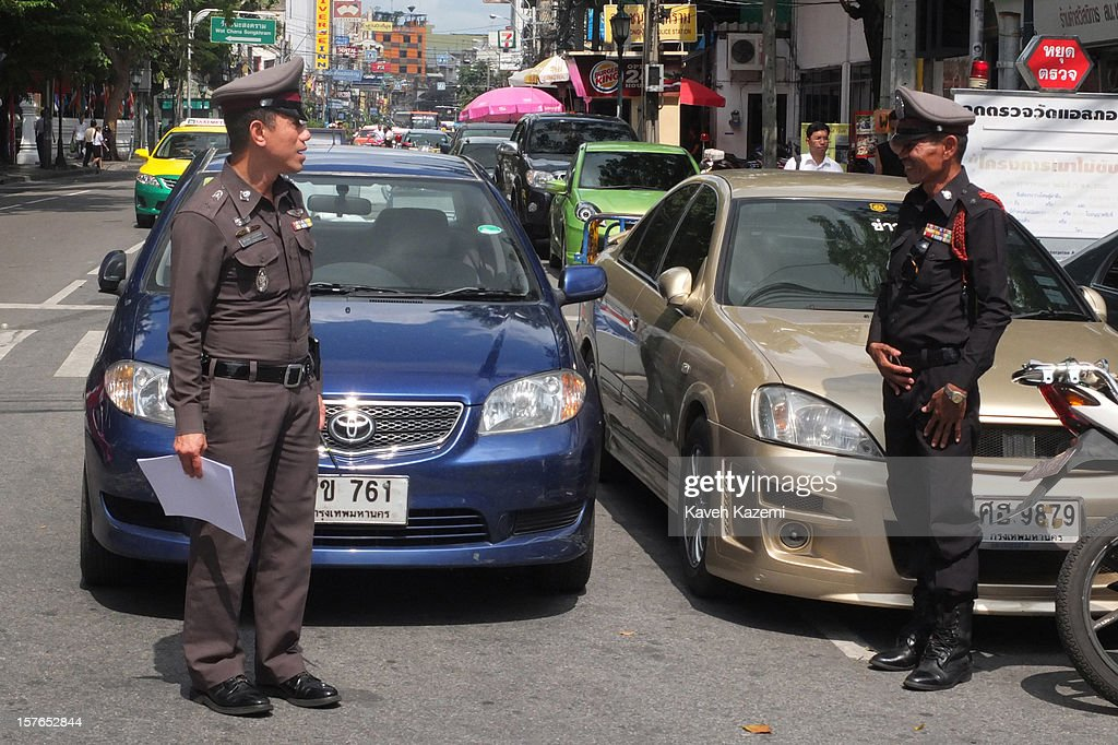 A Thai policeman (R) salutes his commanding officer outside a police station on October 25, 2012 in Bangkok, Thailand.