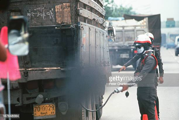 Thai policemen check trucks for pollution on a busy street on the outskirts of Bangkok using a device that checks emissions coming out of the exhaust...