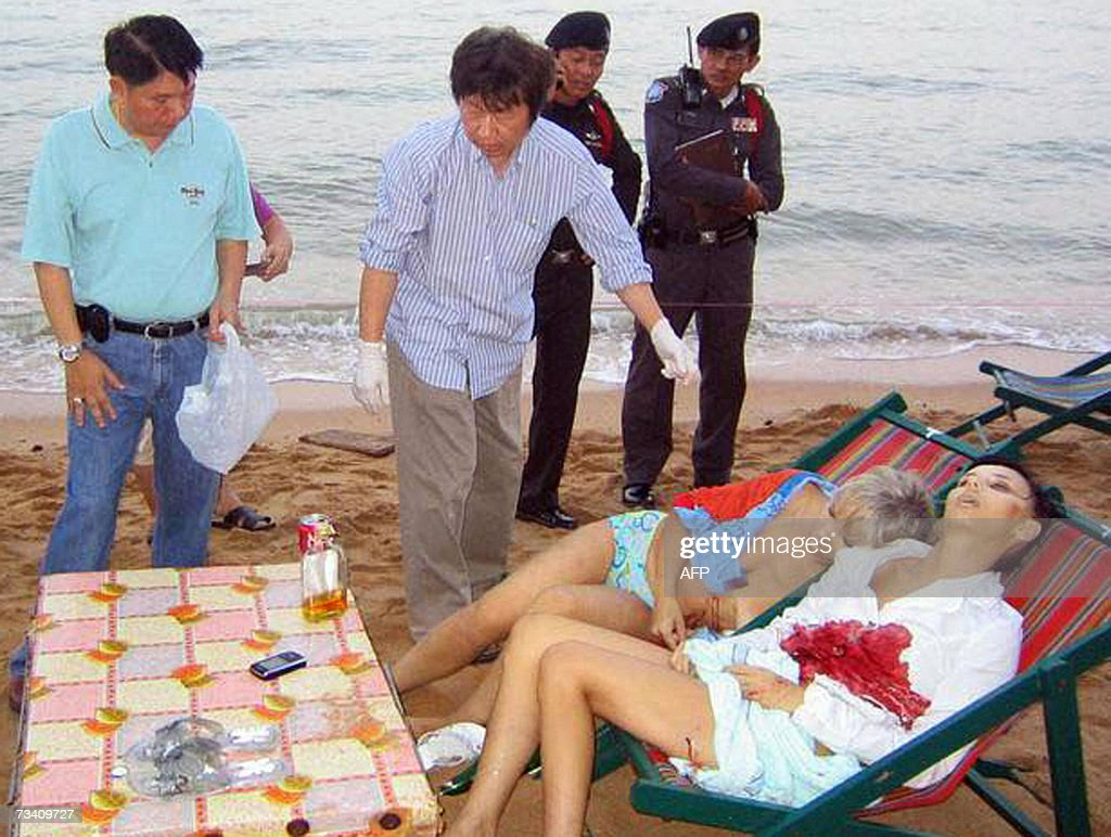 Thai policemen inspect the bodies of two Russian tourists at Jomtien beach Pattaya some 150 kilometres southeast of Bangkok 24 February 2007 Two...