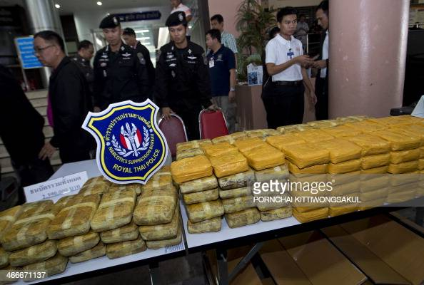 Thai policemen stand guard next to confiscated packages of amphetamine pills during a press conference at the Narcotics Suppression Bureau in Bangkok...