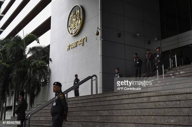 Thai policemen stand guard outside of a criminal court in Bangkok on July 19 2017 A Thai general is among more than 100 defendants facing a verdict...