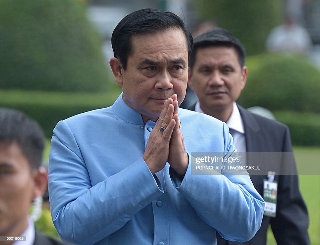 Thai Prime Minister and Army chief General Prayut ChanOCha gives a traditional greeting to the media prior to the first cabinet meeting at Government...