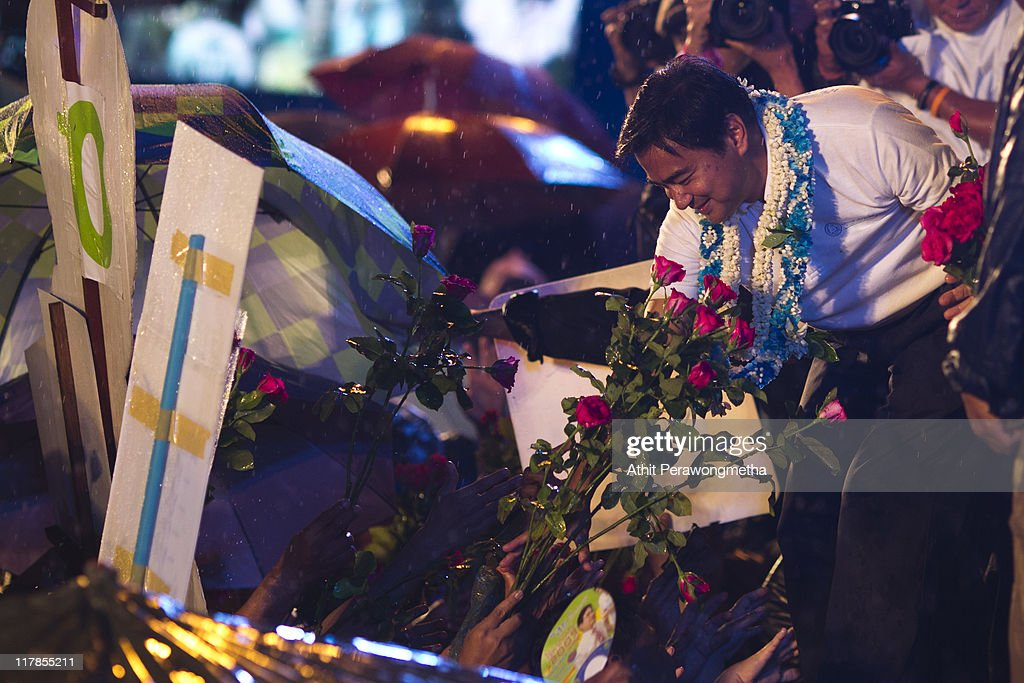 Thai Prime Minister and leader of the Democrat party Abhisit Vejjajiva receives flowers during a final campaign rally under heavy rain at Royal Plaza on July 1, 2011 in Bangkok, Thailand. Thailand's fourth election in seven years on July 3 will see Prime Minister Abhisit Vejjajiva's Democrats go up against the red shirt movement supported Yingluck Shinawatra, the younger sister of fugitive former prime minister Thaksin Shinawatra, who was ousted in a 2006 coup.