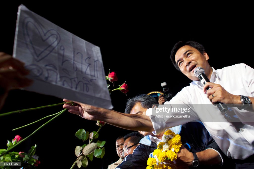 Thai Prime Minister and leader of the Democrat party <a gi-track='captionPersonalityLinkClicked' href=/galleries/search?phrase=Abhisit+Vejjajiva&family=editorial&specificpeople=645779 ng-click='$event.stopPropagation()'>Abhisit Vejjajiva</a> receives flowers from supporters during a rally held at the site of Red Shirt protesters last year on June 23, 2011 in Bangkok, Thailand. Thousands of supporters gathered at Ratchaprasong, Bangkok's prime business and shopping area, to join a major Democrat Party election campaign rally.