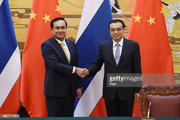 Thai Prime Minister Prayut Chanocha shakes hands with Chinese Premier Li Keqiang during a signing ceremony at the Great Hall of the People on...