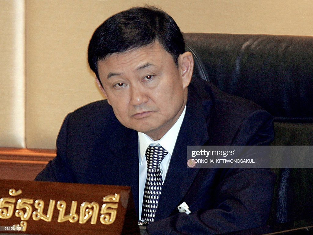 Thai Prime Minister <a gi-track='captionPersonalityLinkClicked' href=/galleries/search?phrase=Thaksin+Shinawatra&family=editorial&specificpeople=220948 ng-click='$event.stopPropagation()'>Thaksin Shinawatra</a> listens to the head of opposition coalition parties and Democrat leader, Abisit Vejjajiva (not in photo) speaks during the no-confidence debate against Transport Minister, Suriya Jungrungreangkit at the Parliament House in Bangkok, 27 June 2005. Abisit said the opposition has found evidence showing that Transportation Minister Suriya Jungrungreangkit had failed to do his job and let the corruption scandal over the purchase of baggae scanners for Bangkok's new airport happened. AFP PHOTO/PORNCHAI KITTIWONGSAKUL