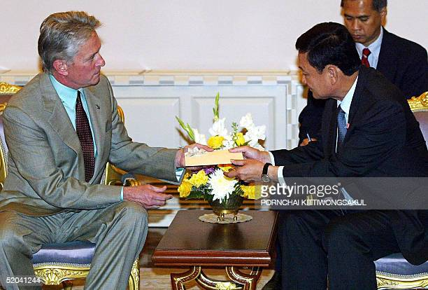 Thai Prime Minister Thaksin Shinawatra recieves a cheque from Hollywood actor Michael Douglas at the Government House in Bangkok 21 January 2005...