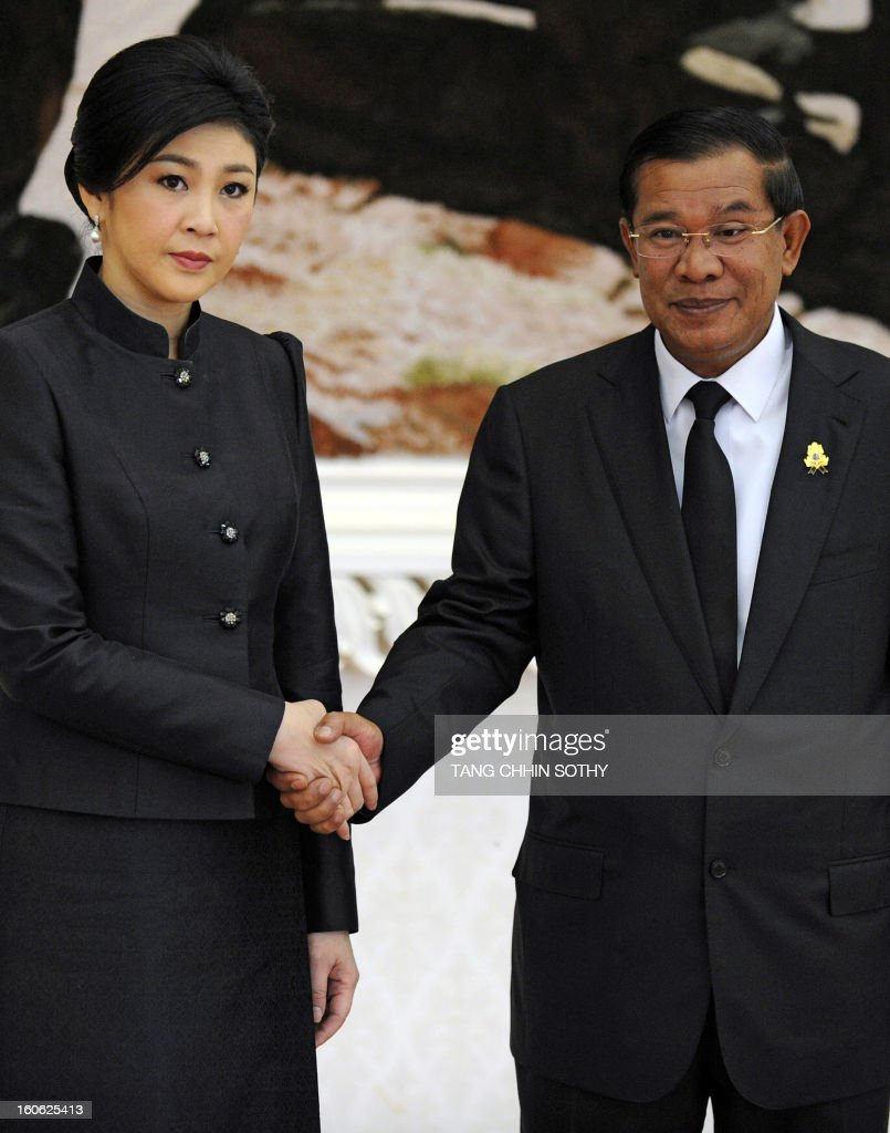 Thai Prime Minister Yingluck Shinawatra (L) shakes hands with Cambodian Prime Minister Hun Sen (R) during a meeting at the Peace Palace in Phnom Penh on February 4, 2013. Yingluck arrived here to pay her respects and attend the funeral of the late former king Norodom Sihanouk ahead of his cremation on February 4. AFP PHOTO / TANG CHHIN SOTHY