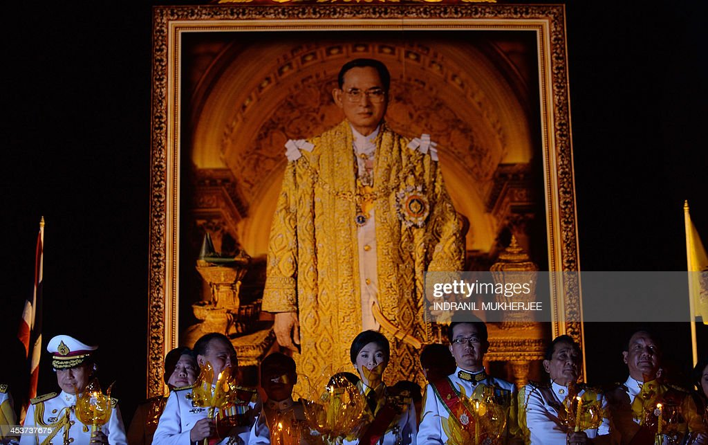 Thai Prime Minister Yingluck Shinawatra (C) sings the national anthem while standing in front of a portrait of King Bhumibol Adulyadej to celebrate the 86th birthday of The King in Bangkok on December 5, 2013. Thailand's revered King Bhumibol Adulyadej urged the nation to work together for 'stability' in a speech on December 5 on his 86th birthday, marked by an easing of tensions after violent anti-government protests. AFP PHOTO/Indranil MUKHERJEE
