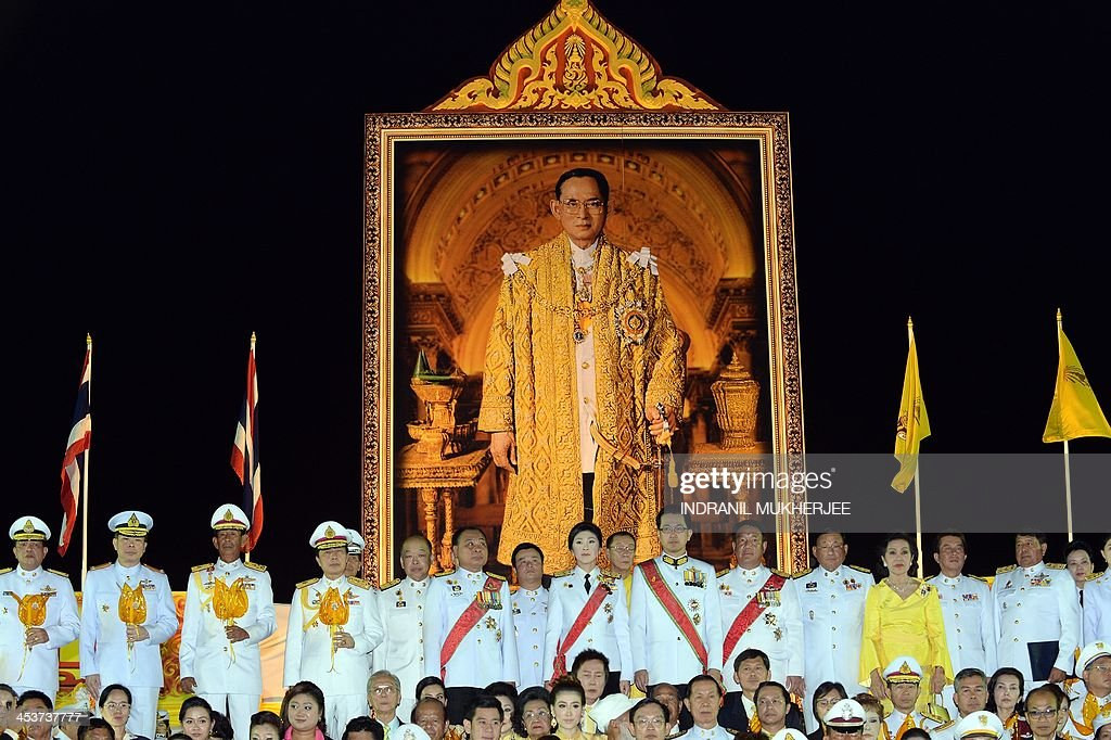 Thai Prime Minister Yingluck Shinawatra (C, top row) sings the national anthem with civilian, government and defence officials while standing in front of a photograph of King Bhumibol Adulyadej to celebrate the 86th birthday of The King in Bangkok on December 5, 2013. Thailand's revered King Bhumibol Adulyadej urged the nation to work together for 'stability' in a speech on December 5 on his 86th birthday, marked by an easing of tensions after violent anti-government protests. AFP PHOTO/Indranil MUKHERJEE