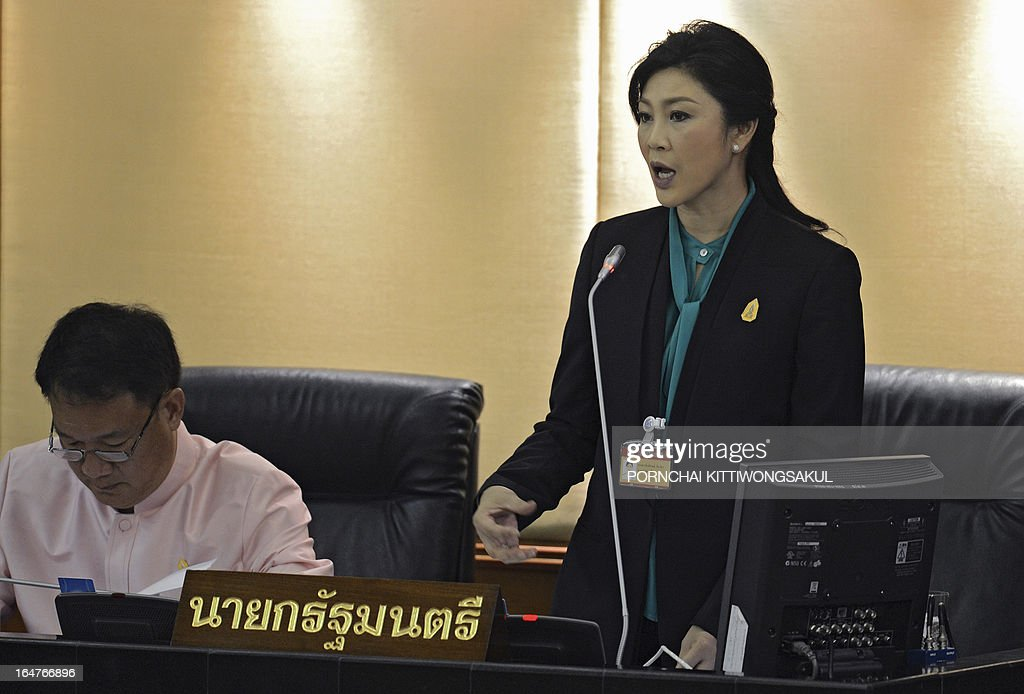 Thai Prime Minister Yingluck Shinawatra (R) speaks next to Finance Minister Kittirat Na-Ranong (L) during a debate on the 2-trillion-baht loan bill at Parliament, in Bangkok on March 28, 2013. The 2-trillion-baht (USD 68 billion USD) loan bill would be used to boost the national infrastructure and investment projects for the Association of South east Asian Nations Economic Community (AEC).