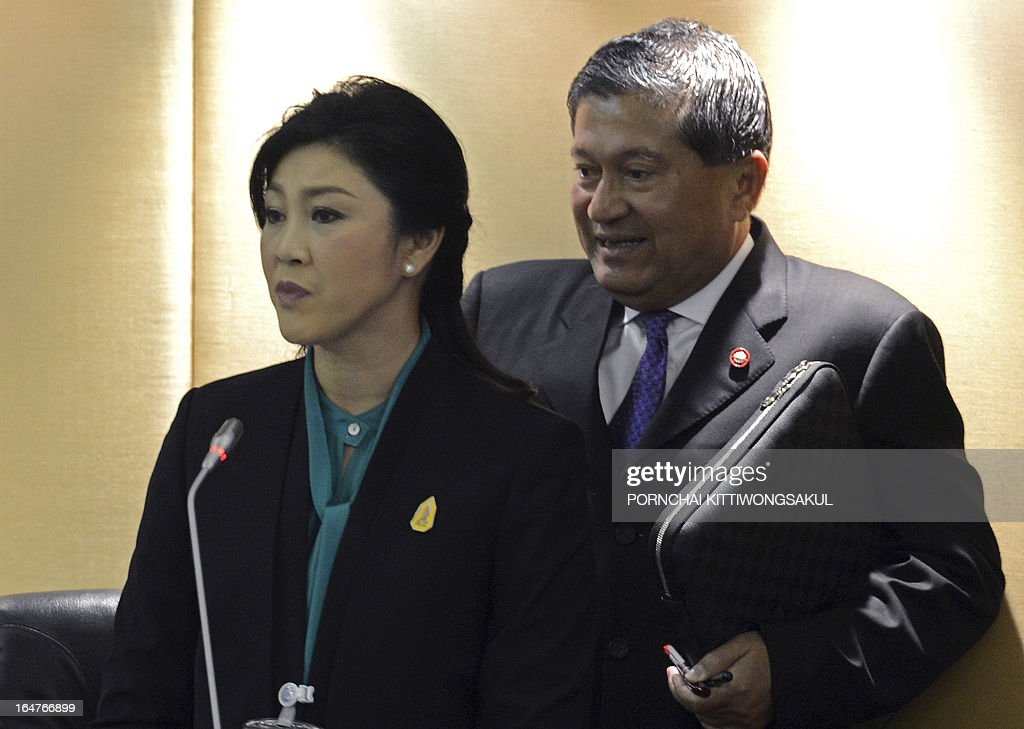 Thai Prime Minister Yingluck Shinawatra (L) speaks while deputy Prime Minister Chalerm Yoobamrung (R) walks past during a debate on the 2-trillion-baht loan bill at Parliament, in Bangkok on March 28, 2013. The 2-trillion-baht (USD 68 billion USD) loan bill would be used to boost the national infrastructure and investment projects for the Association of South east Asian Nations Economic Community (AEC). AFP PHOTO/PORNCHAI KITTIWONGSAKUL