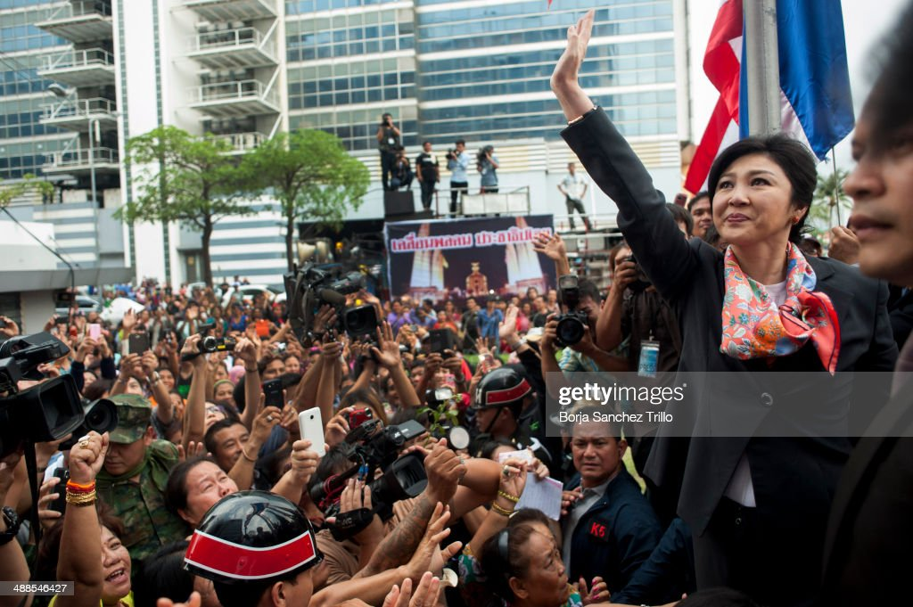 Thai Prime Minister, Yingluck Shinawatra, waves to her supporters at the Defence Permanent Secretary Office on May 7, 2014 in Bangkok, Thailand. Thai Constitutional Court has ruled that Thai Prime Minister, Yingluck Shinawatra, and 9 cabinet ministers to step down. The charges relate to complaints filed by senators which suggested that Yingluck's party improperly transferred her security chief in 2011.