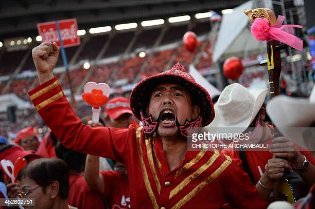 A Thai progovernment Red Shirt supporter in traditional costume shouts slogans during a rally at a stadium in Bangkok on November 30 2013 Tensions...
