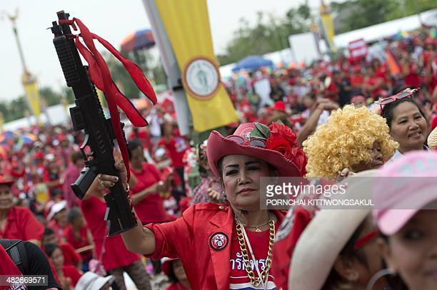 Thai progovernment 'Red Shirts' holds a plastic machine gun during a rally at Phutthamonthon suburb of Bangkok on April 5 2014 Thousands of Thai...