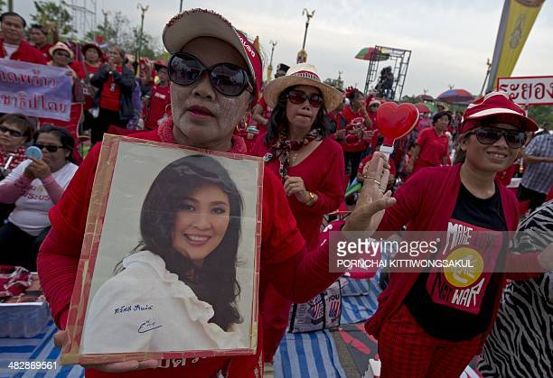 Thai progovernment 'Red Shirts' holds a portrait of Prime Minister Yingluck Shinawatra during a rally at Phutthamonthon suburb of Bangkok on April 5...
