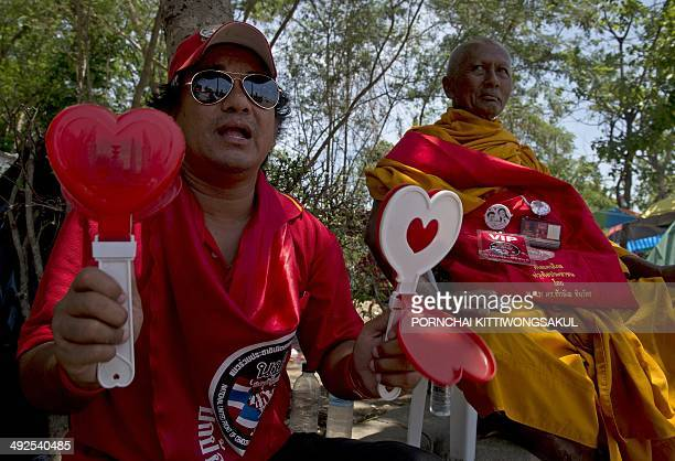 Thai progovernment ''Red shirts'' protester shakes clapper during a rally on the outskirts of Bangkok on May 21 2014 Thailand's military called...