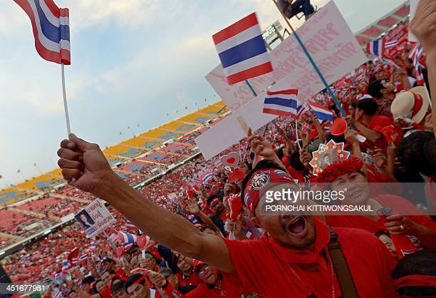 Thai progovernment 'Red Shirts' wave national flag as they gather at Rajamangala stadium in Bangkok on November 24 2013 Thai progovernment 'Red...