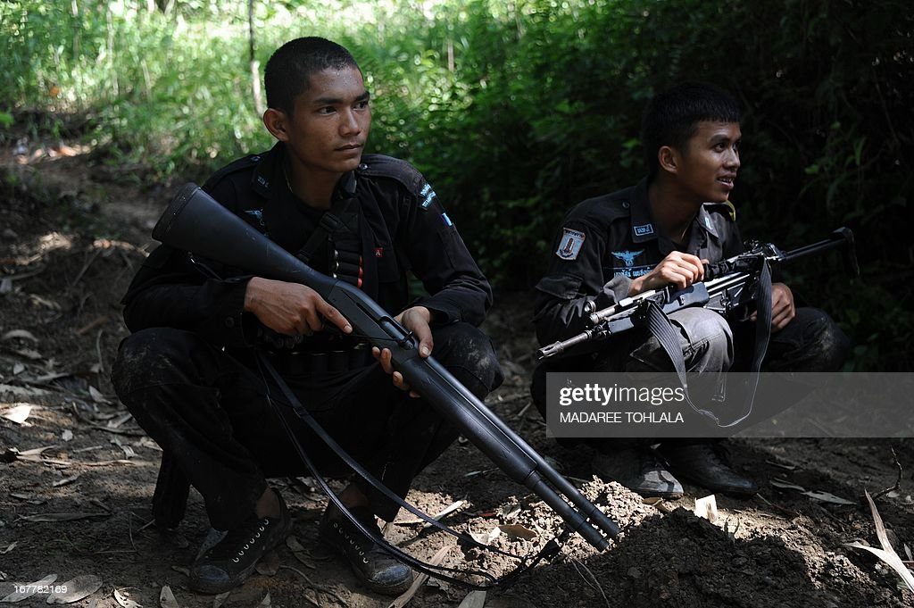 Thai rangers guard the area where a suspected separatist militant (not pictured) was shot dead during a clash with army rangers in the Cha-nea district of Thailand's restive southern province of Narathiwat on April 30, 2013. More than 5,500 people have been killed in Thailand's Muslim-majority south since 2004, with shadowy insurgent groups blamed for near-daily bombings and shootings. AFP PHOTO / Madaree TOHLALA