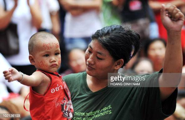 A Thai 'Red Shirt' antigovernment protester teaches her son how to raise his fist prior to Red Shirts leaders' announcement they will negotiate with...