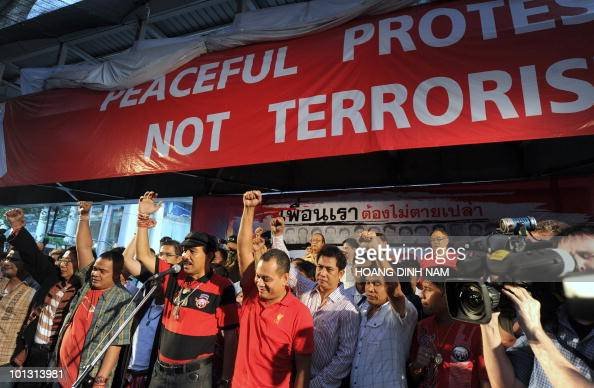 Thai 'Red Shirt' antigovernment protesters' leaders raise their fists as they address a 'Red Shirts' rally to announce an agreement to negotiate with...