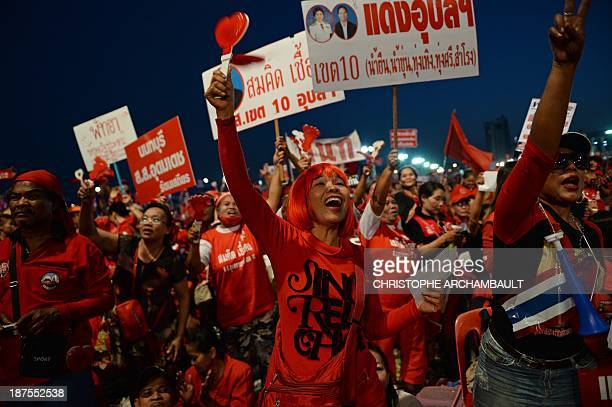 Thai Red Shirts supporters hold placards and shout slogans during a rally in Bangkok on November 10 2013 Thousands of Thai progovernment 'Red Shirts'...