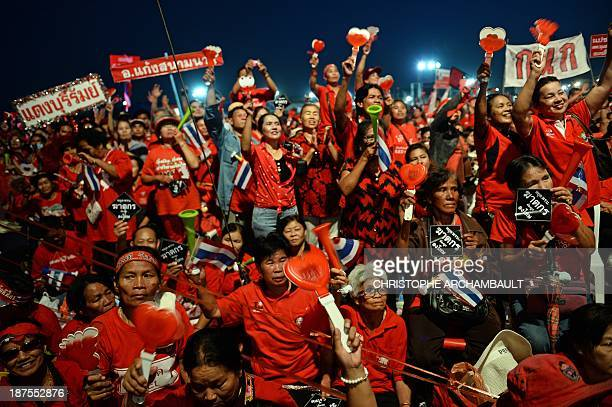 Thai Red Shirts supporters wave clappers and hold placards during a rally in Bangkok on November 10 2013 Thousands of Thai progovernment 'Red Shirts'...