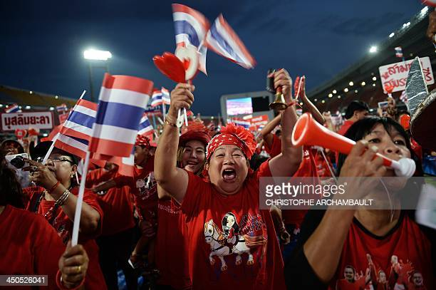 Thai Red Shirts supporters wave clappers and national flags during a rally at a stadium in Bangkok on November 19 2013 Thai Premier Yingluck...