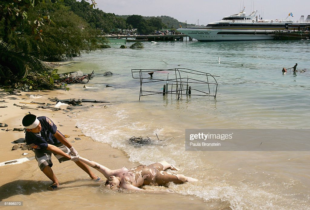 A Thai rescue worker pulls a body out of the bay that washed ashore on December 28 2004 in Phi Phi Village Thailand On Phi Phi island hundreds were...