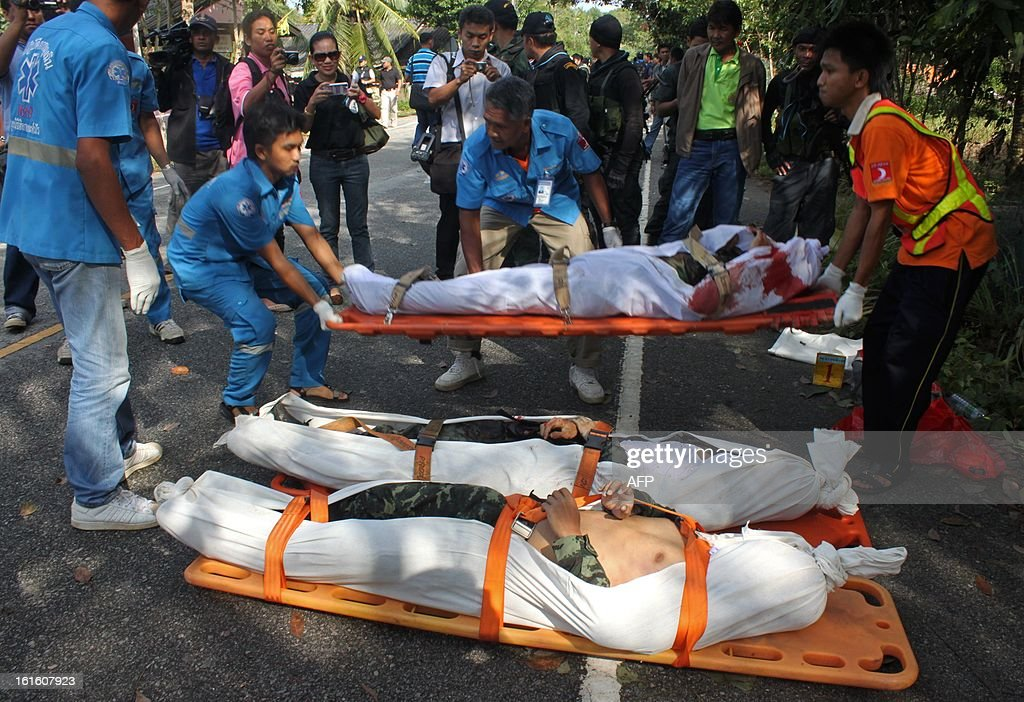 Thai rescue workers carry dead suspected insurgents who were killed when they attacked a military base in Thailand's restive southern province of Narathiwat on February, 13, 2013. Scores of heavily armed gunmen stormed a military base in unrest-plagued southern Thailand, an army spokesman said, in a major assault that left at least 16 militants dead.