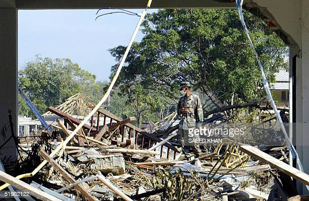 Thai rescuer walks among the debris from the washed away resorts and bangalows on the shoreline of Khao Lak beach 30 December 2004 The final death...