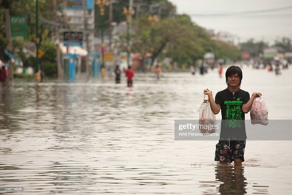 A thai resident carries his belongings as floods continue to hit Pathum Thani province on October 14, 2011 in Pathum Thani, north of Bangkok,Thailand. Crews of public workers, soldiers and volunteers are evacuating residents from flooded areas north of Bangkok as efforts continue to protect the capital from increased rainfall and rising tides during the worst floods to hit the country for decades.