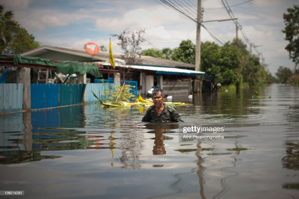 A thai resident stands in front of his house as floods continue to hit Pathum Thani province on October 14, 2011 in Pathum Thani, north of Bangkok,Thailand. Crews of public workers, soldiers and volunteers are evacuating residents from flooded areas north of Bangkok as efforts continue to protect the capital from increased rainfall and rising tides during the worst floods to hit the country for decades.