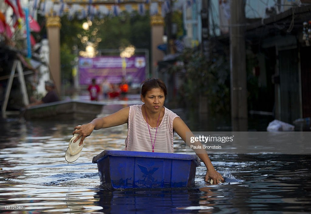 A Thai resident uses sandals as paddles as she moves down a flooded street November 7, 2011 in Bangkok, Thailand. Over seven major industrial parks in Bangkok and thousands of factories have been closed in the central Thai province of Ayutthaya and Nonthaburi with millions of tons of rice damaged. Thailand is experiencing the worst flooding in over 50 years which has affected more than nine million people.