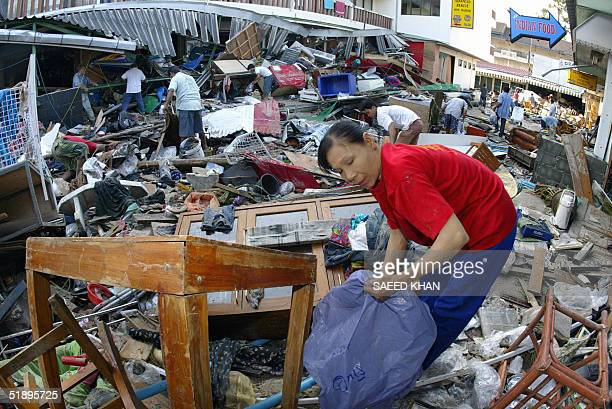 Thai residents collect their belongings from the debris of destroyed bars along Pathong beach on the southern Thai island of Phuket 27 December 2004...